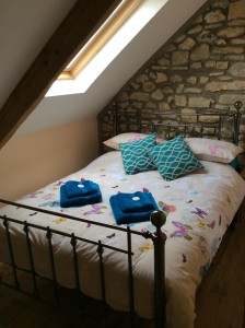 Double bedroom with original stone wall feature and beams